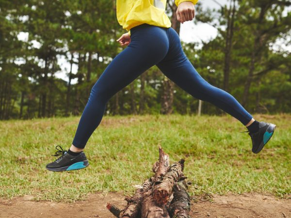 Legs of sporty woman jumping over logs in forest